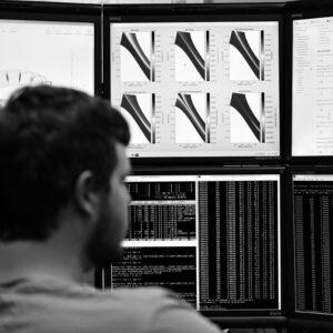 a person looking at computer monitors