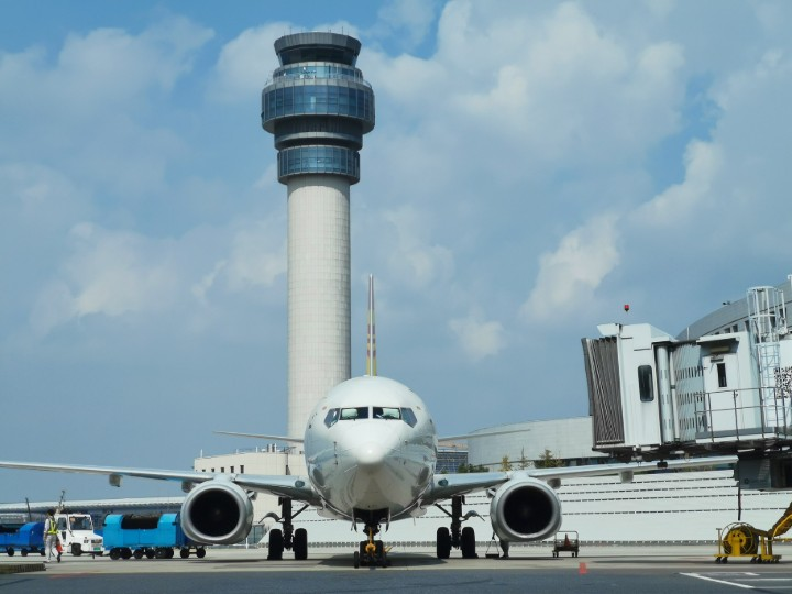 an aeroplane in front of a control tower