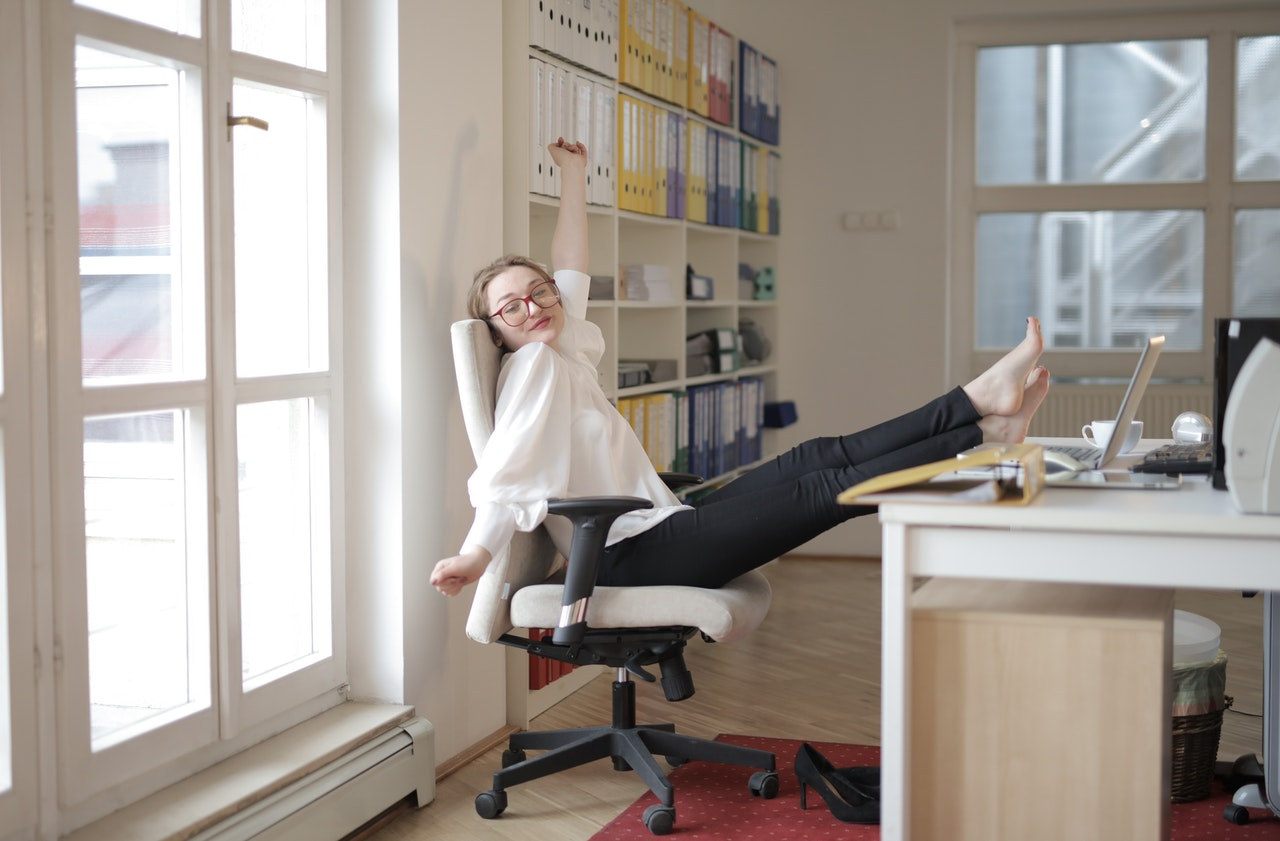 a woman stretching on a work chair