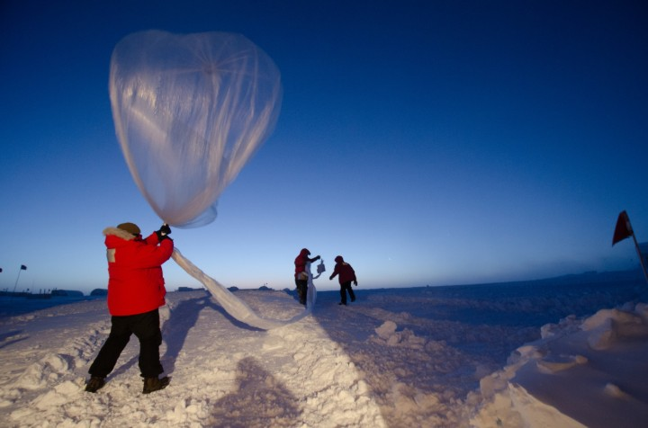 people letting off a weather balloon in snowy conditions