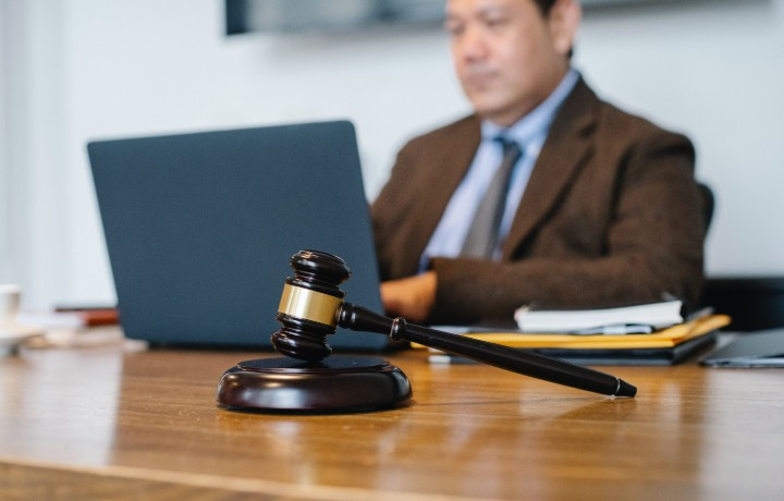 a man sat at a computer with a gavel in front