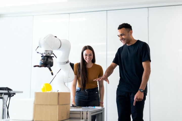 a man and a woman looking at a robotic arm